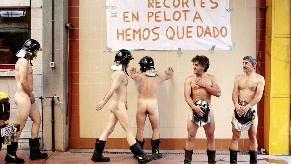 "Firefighters in Asturias, northern Spain, prepare to pose naked with a sign that reads, ""With so many funding cuts, we are left naked."""
