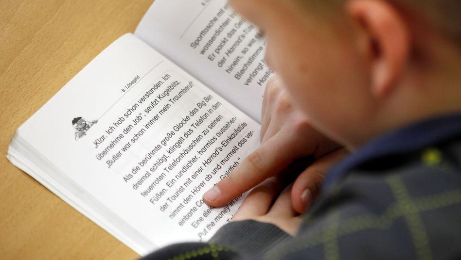 Ein Junge liest in seinem Lesebuch (Symbolbild).