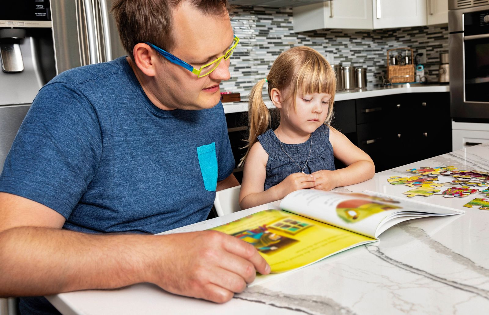 A father sitting down with his young daughter in the kitchen to read a book: Edmonton, Alberta, Canada PUBLICATIONxINxGE