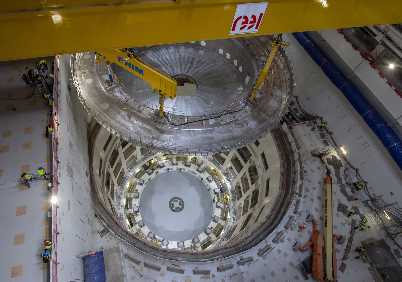 Cranes lift ITER?s cryostat base into the tokamak pit to begin reactor assembly.