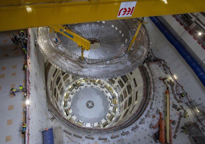 Kräne hieven die über 1200 Tonnen schere Kryostat-Basis aus Stahl in die Reaktorhülle.