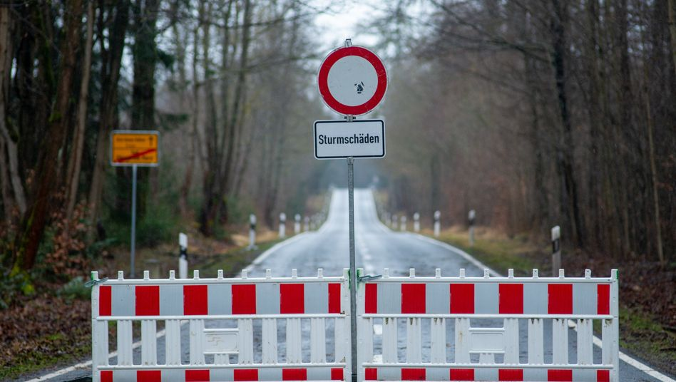 """""""Sturmschäden"""" steht auf einem Schild vor einer Straßensperrung"""