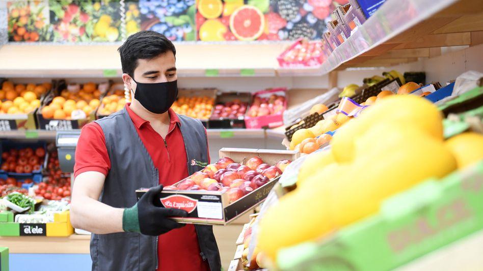 Ein Supermarkt-Mitarbeiter in Bayern mit Maske