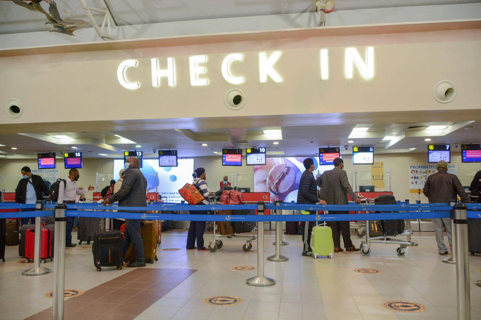July 31, 2020, Nairobi, Kenya: Passengers in facemasks queue at a check-in point at Jomo Kenyatta International Airport