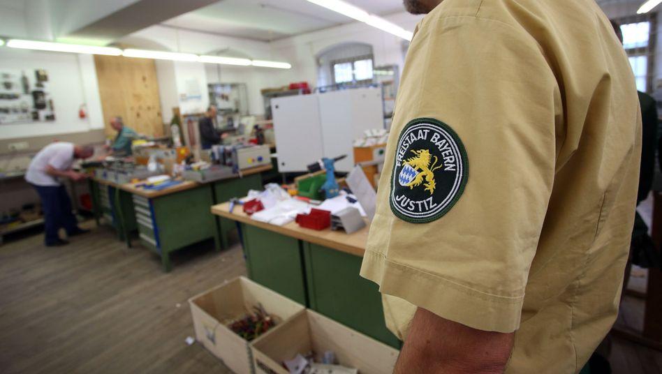 Gefängnismitarbeiter und Häftlinge im Elektronikbetrieb der Justizvollzugsanstalt