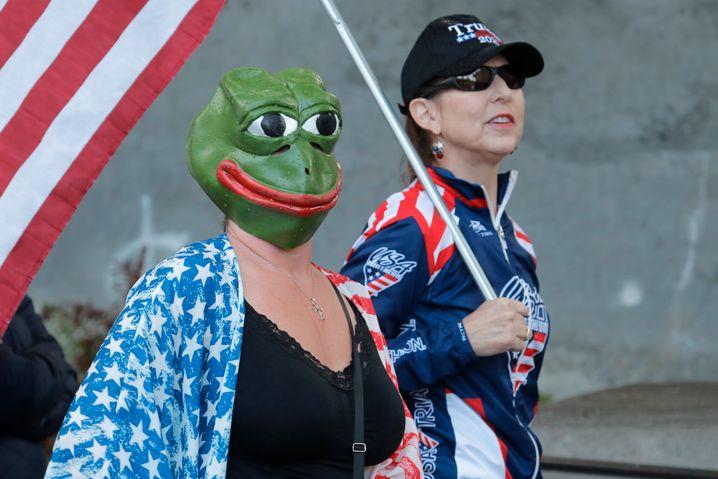 Eine Demonstrantin trägt bei einem Protest gegen Corona-Maßnahmen im Mai im US-Bundesstaat Washington eine Maske von Pepe the Frog. Beim Sturm auf das Kapitol sangen Angreifer Lieder eines Musikers, der sich nach der bei TheDonald-Anhängern beliebten Comicfigur benannt hat