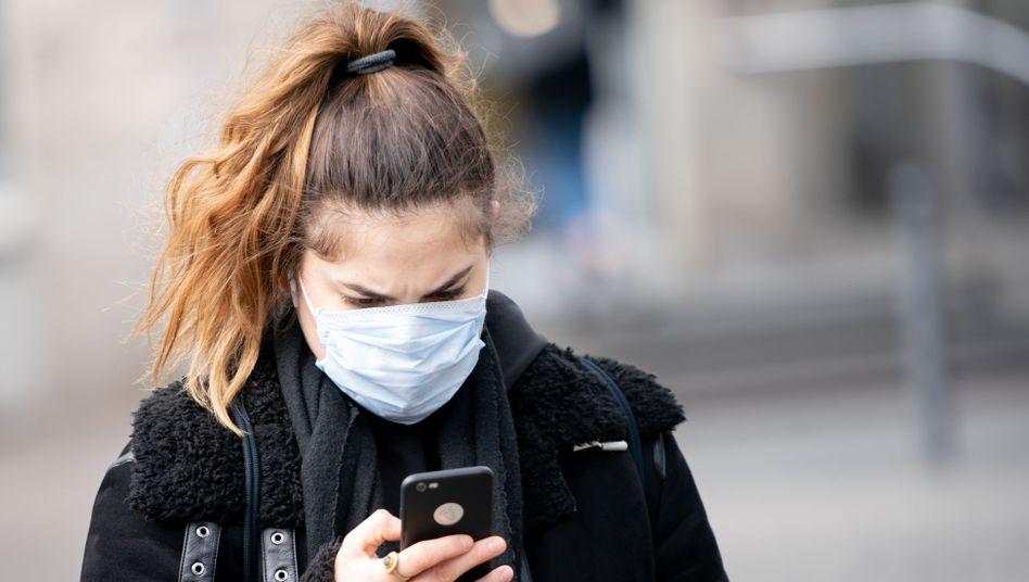 Smartphone-Nutzerin mit Mundschutz (Symbolbild): Ab heute gibt es die Anti-Virus-App auch in Deutschland