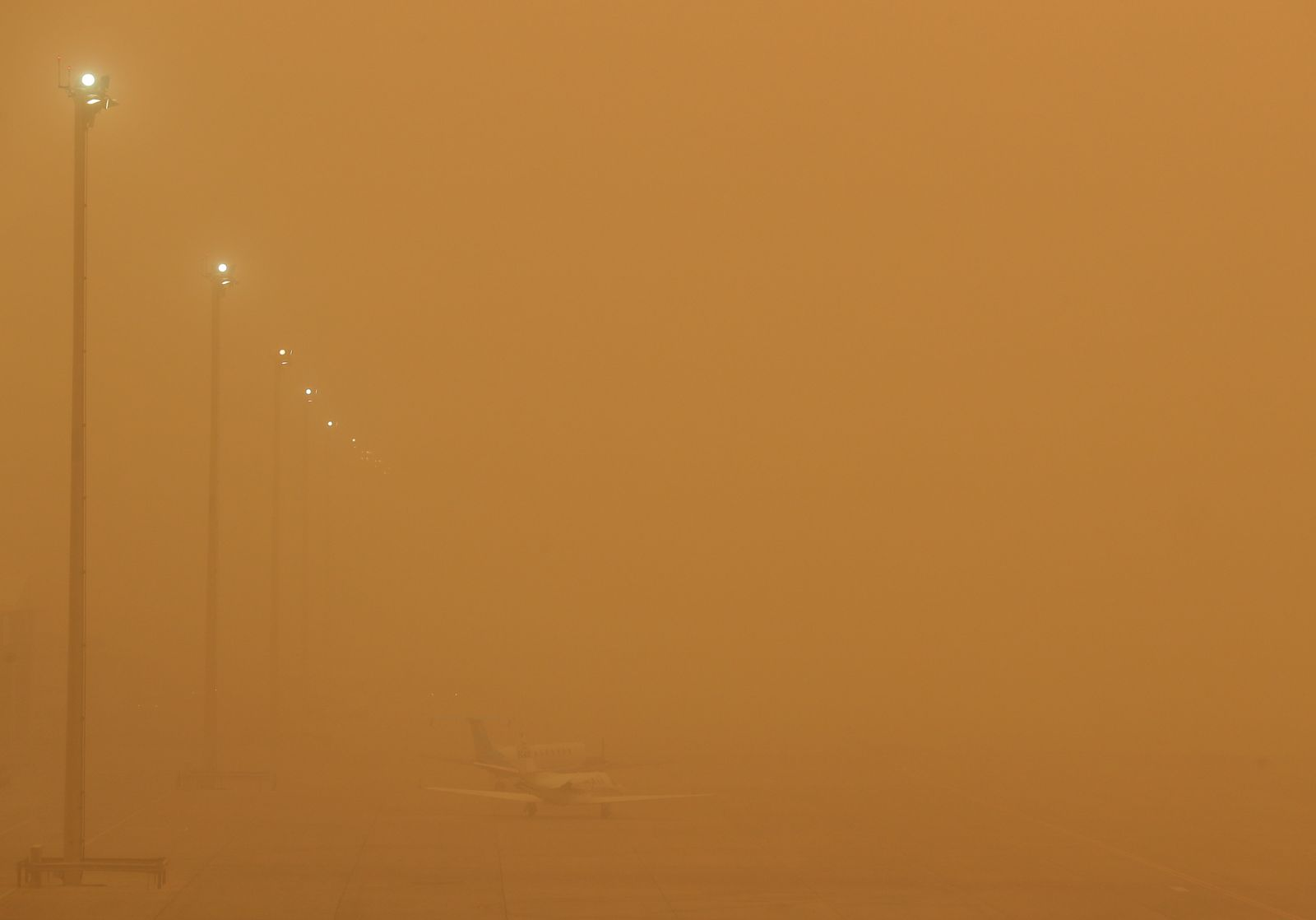 "Planes are seen parked on the tarmac during a sandstorm blown over from North Africa known as ""calima"" at Las Palmas Airport"