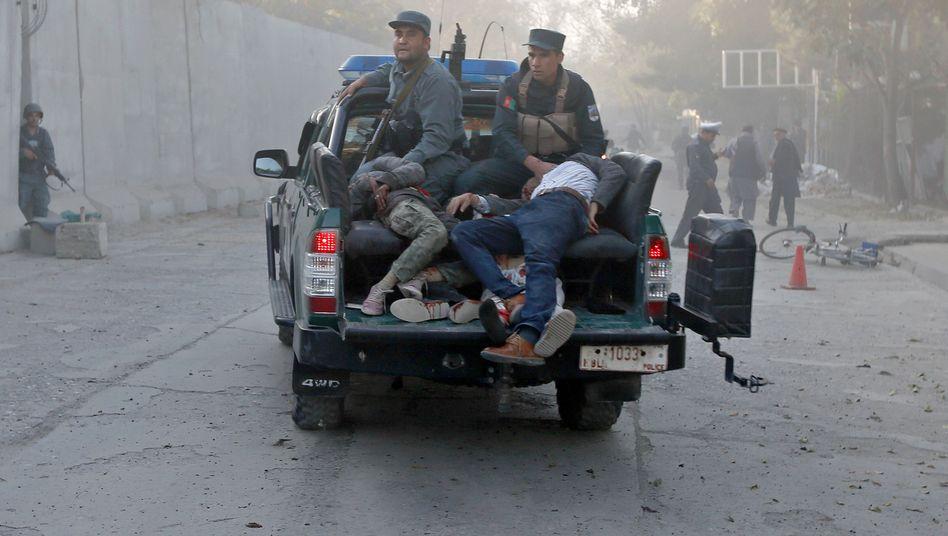 Polizisten transportieren Verletzte vom Anschlagsort ab