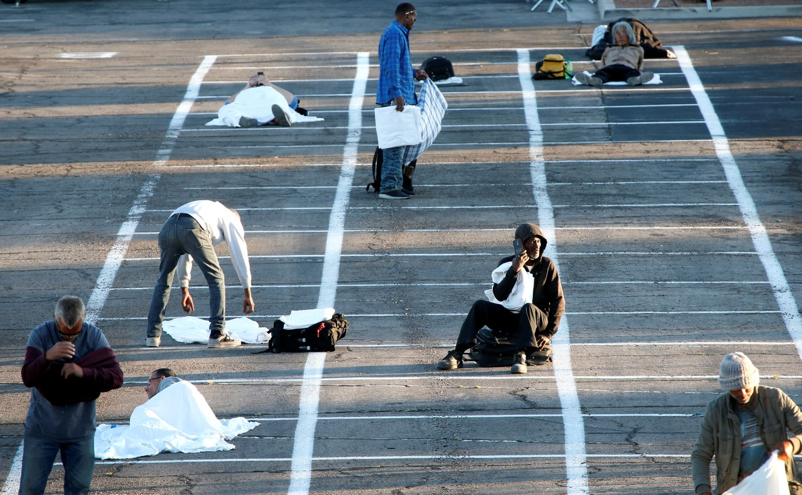 Homeless people get settled in a temporary parking lot with spaces marked for social distancing in Las Vegas