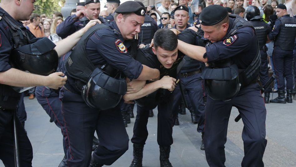 Polizisten halten einen Mann während einer nicht genehmigten Kundgebung im Zentrum von der Stadt fest