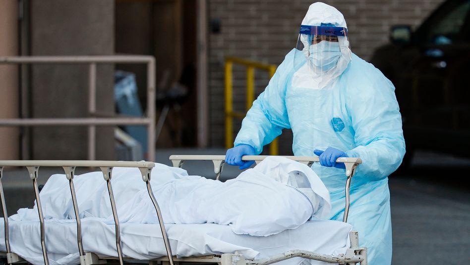 Ein medizinischer Mitarbeiter in Schutzkleidung rollt eine Leiche zu einem Kühlanhänger: Auch in New York gibt es Todesopfer