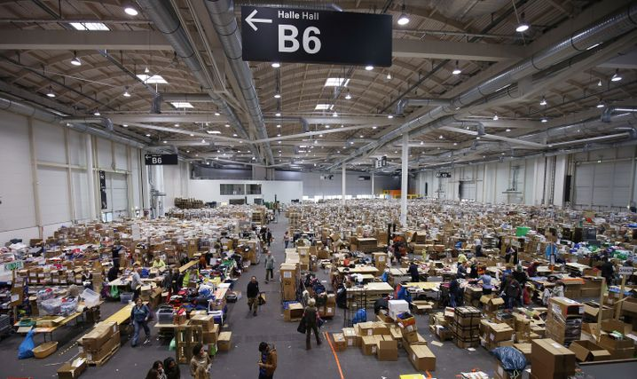"Volunteers help sort clothing donations for refugees at Hamburg's trade fair center: ""I do believe that we in Germany will speak a different language in 10 years' time."""