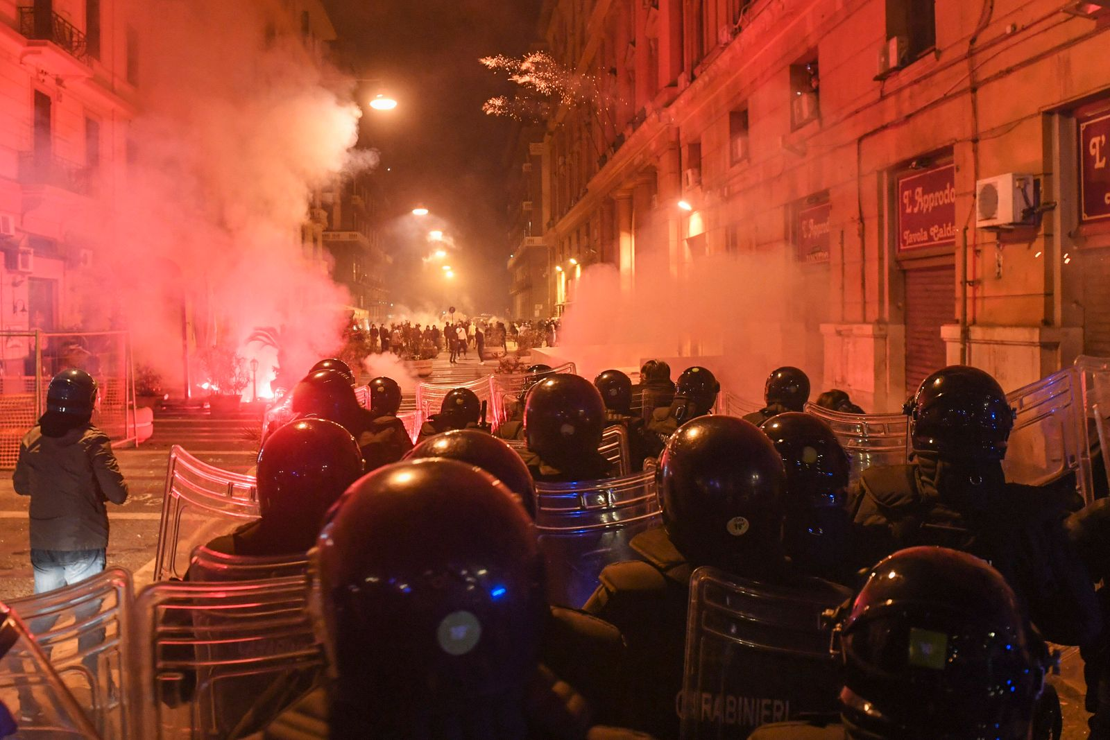 Hundreds of people clash against police during the protest over the curfew and the prospect of lockdown in Naples. The