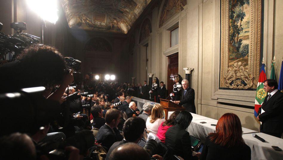 Italy's new designated prime minister, Mario Monti, addresses the press in Rome on Sunday.