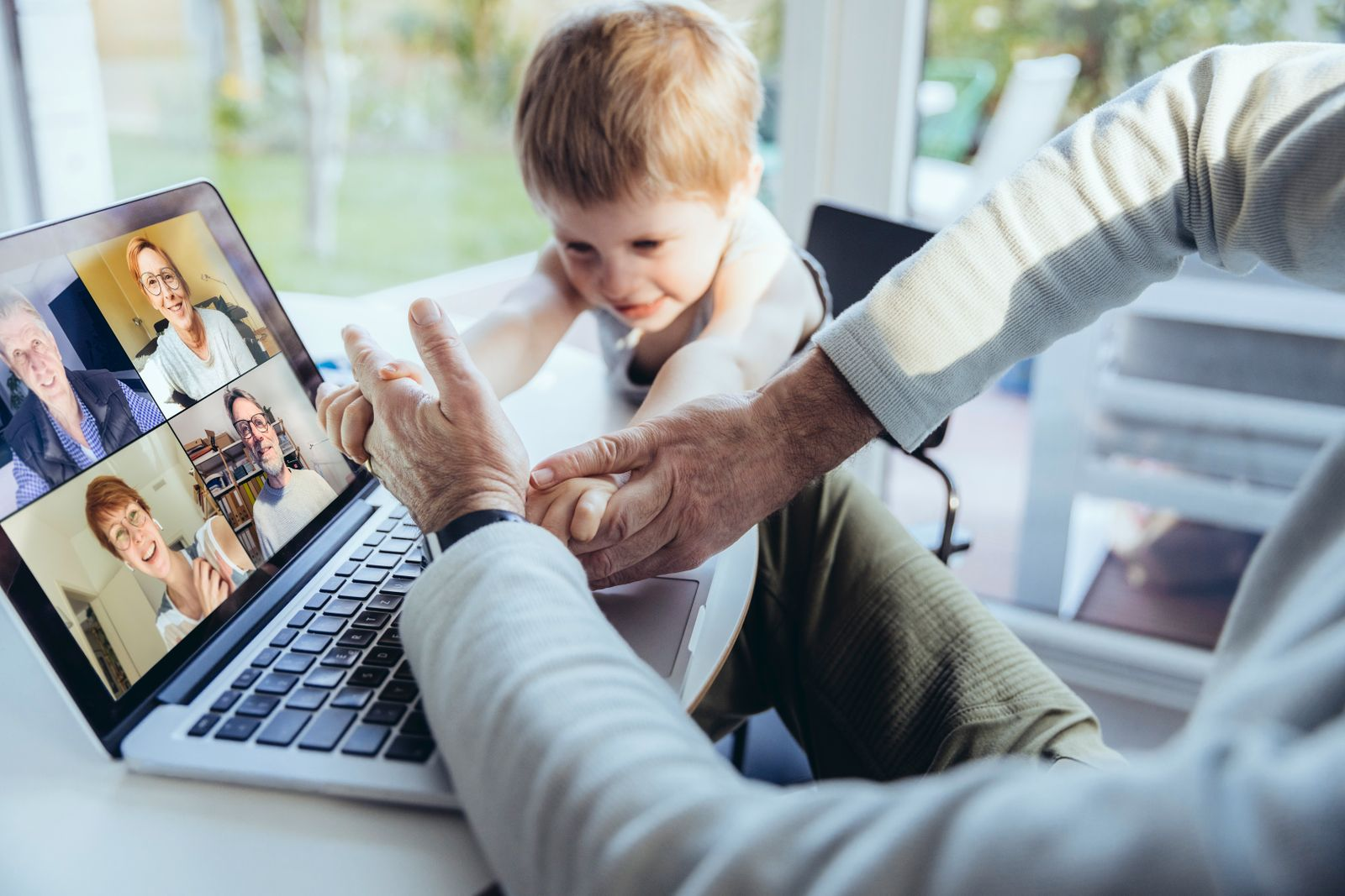 Little boy interrupting father's video conference at home