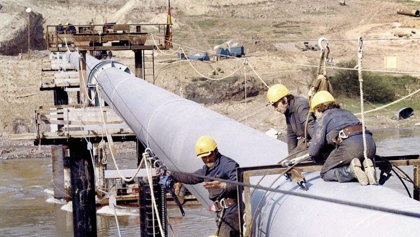 DDR-Monteure führen eine Erdgasleitung über den ukrainischen Fluss Dnjestr, 1983.