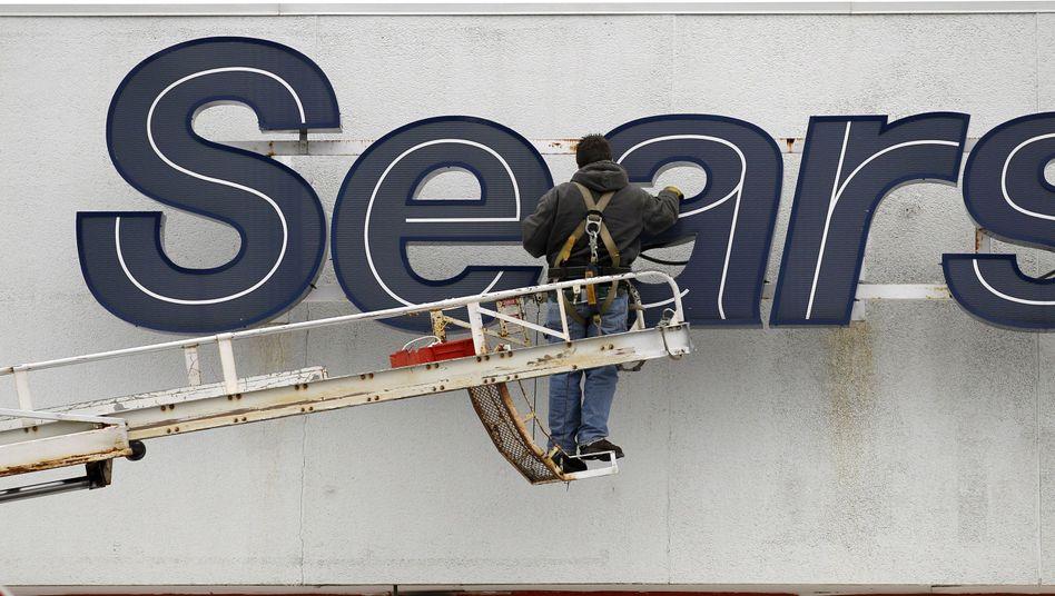Arbeiter repariert ein Logo von Sears