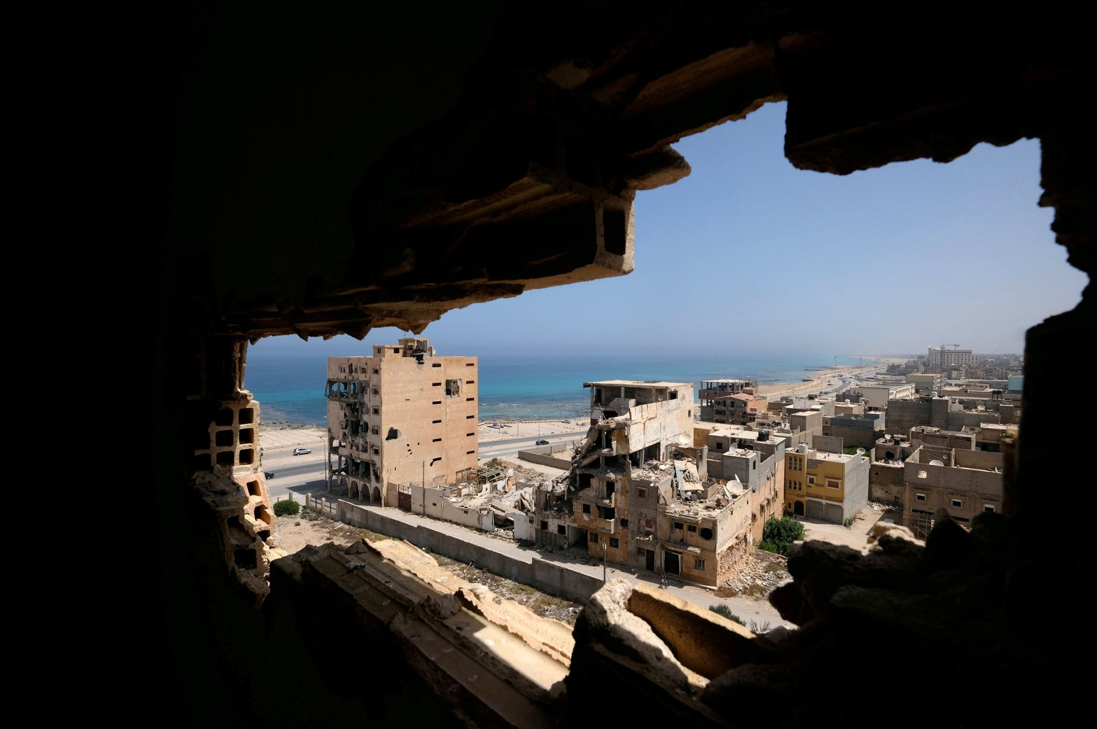 Destroyed buildings are seen through a hole in Benghazi lighthouse after it was severely damaged by years of armed conflict, in Benghazi