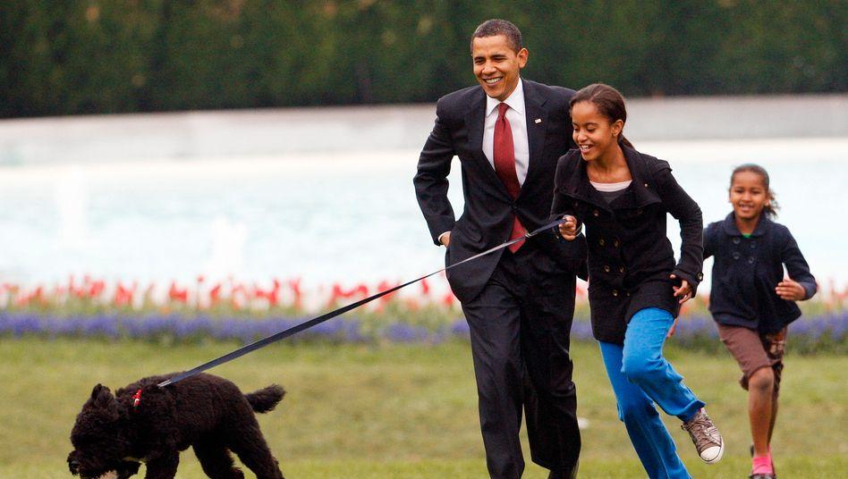 Malia und Sasha Obama spielen 2009 vor dem Weißen Haus mit Hund Bo
