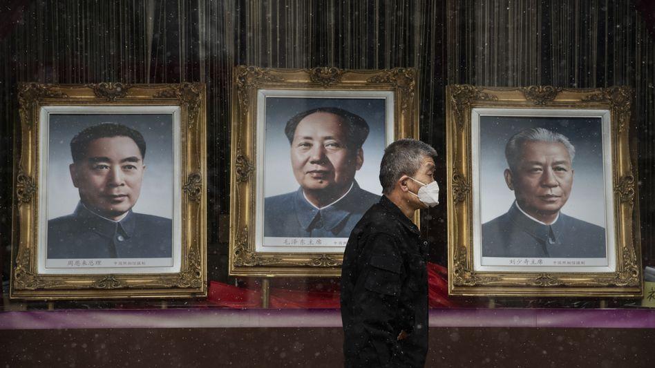 """Ein Mann in einem Einkaufszentrum in Peking, in der Mitte der kommunistische Staatsgründer Mao (Februar 2020): """"Nicht die Hilfslieferungen aus China sind ein Problem, sondern die Propaganda"""""""