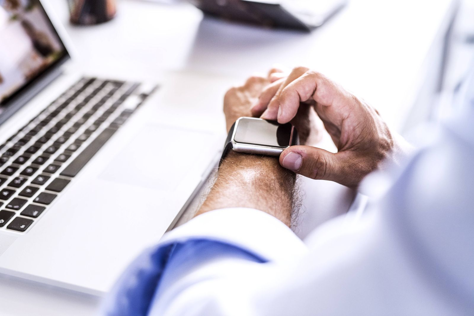 Close up of businessman at desk with laptop using smartwatch model released Symbolfoto property