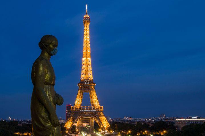 Bronzestatue mit Maske vor dem Eiffelturm