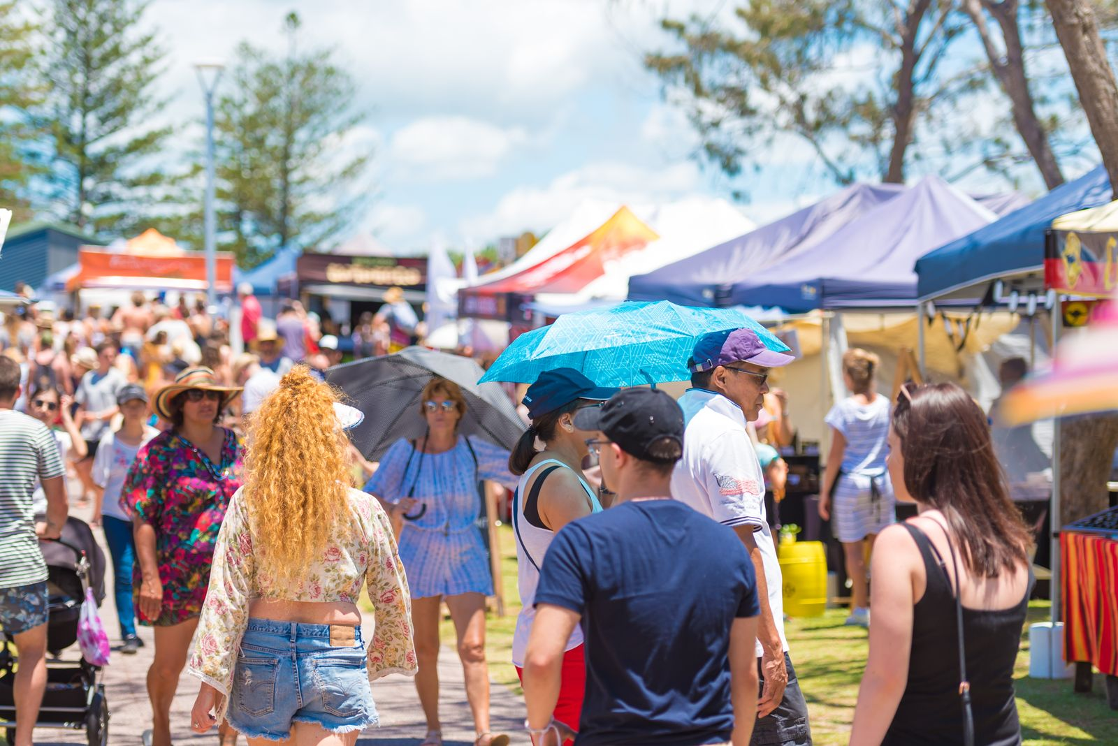 People shopping at festival stall on outdoor fair in Byron Bay, NSW, Australia