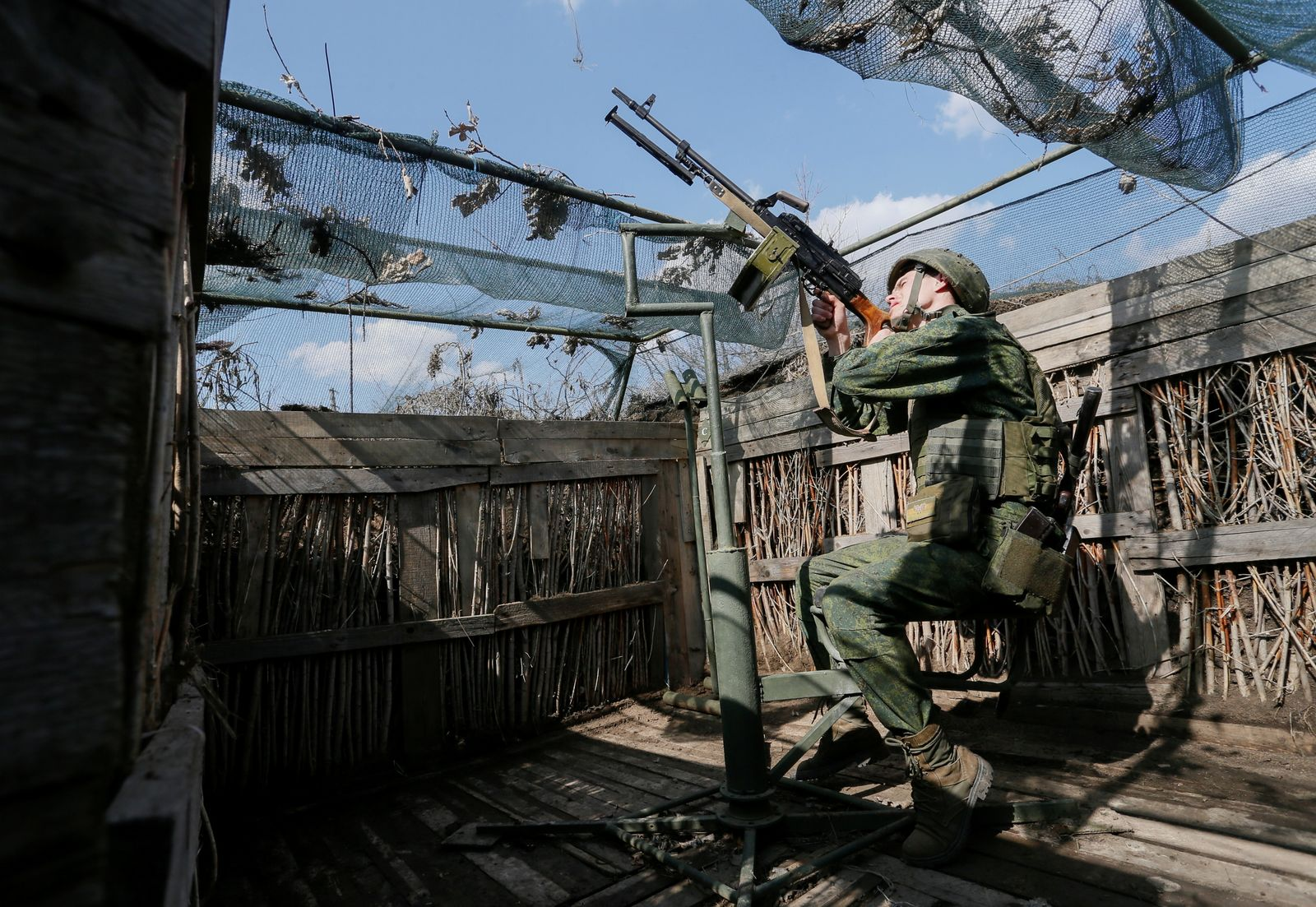 A militant of the self-proclaimed Donetsk People's Republic points a weapon at frontline positions south of Donetsk