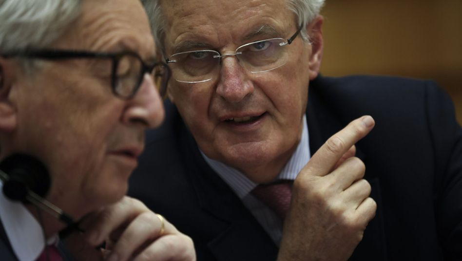 Michel Barnier speaks to European Commission President Jean-Claude Juncker