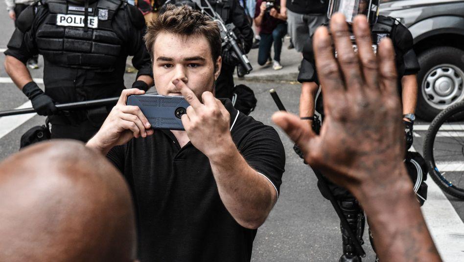 Handykamera und Stinkefinger: Dieser Mann versucht, einen Gegendemonstranten zu provozieren