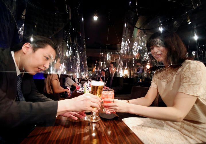 Wie ein Goldfischglas ragen Acrylschirme über den Gesichtern dieser Gäste in einer Bar in Tokio