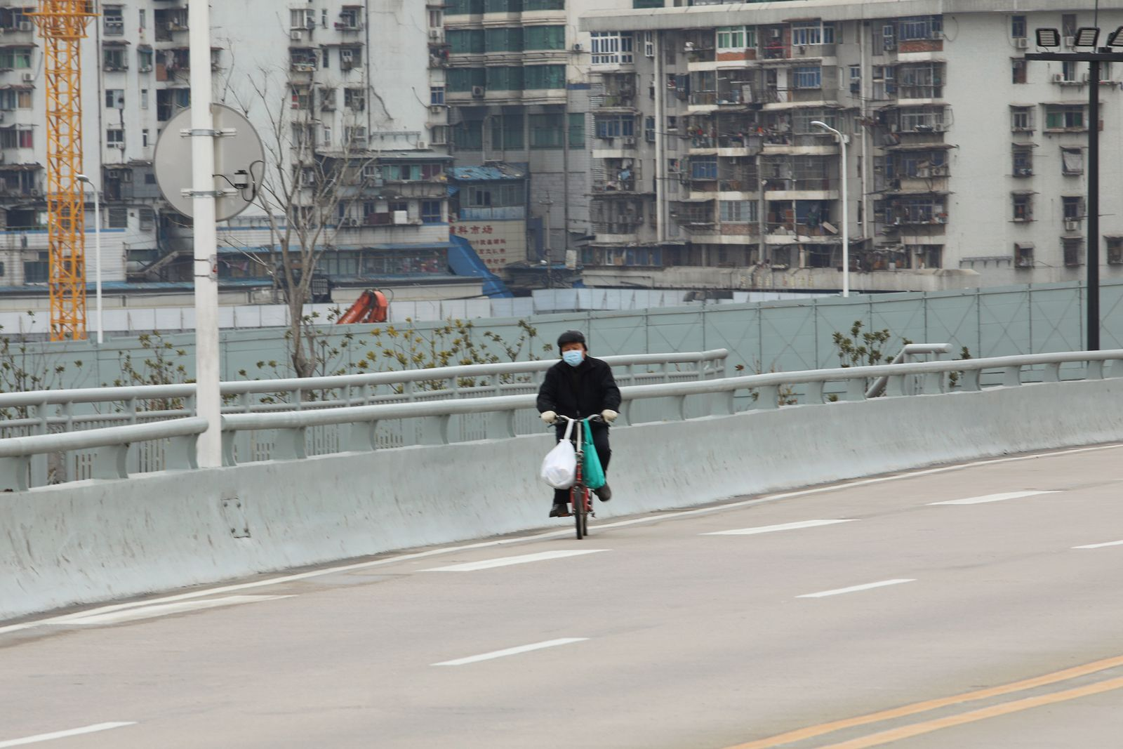 Man wearing a face mask rides a bicycle past residential buildings following an outbreak of the novel coronavirus in Wuhan