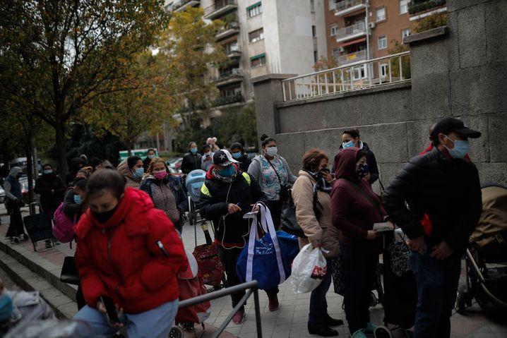 Hilfsbedürftige Spanierinnen und Spanier warten im November 2020 auf die Verteilung von Lebensmittelspenden