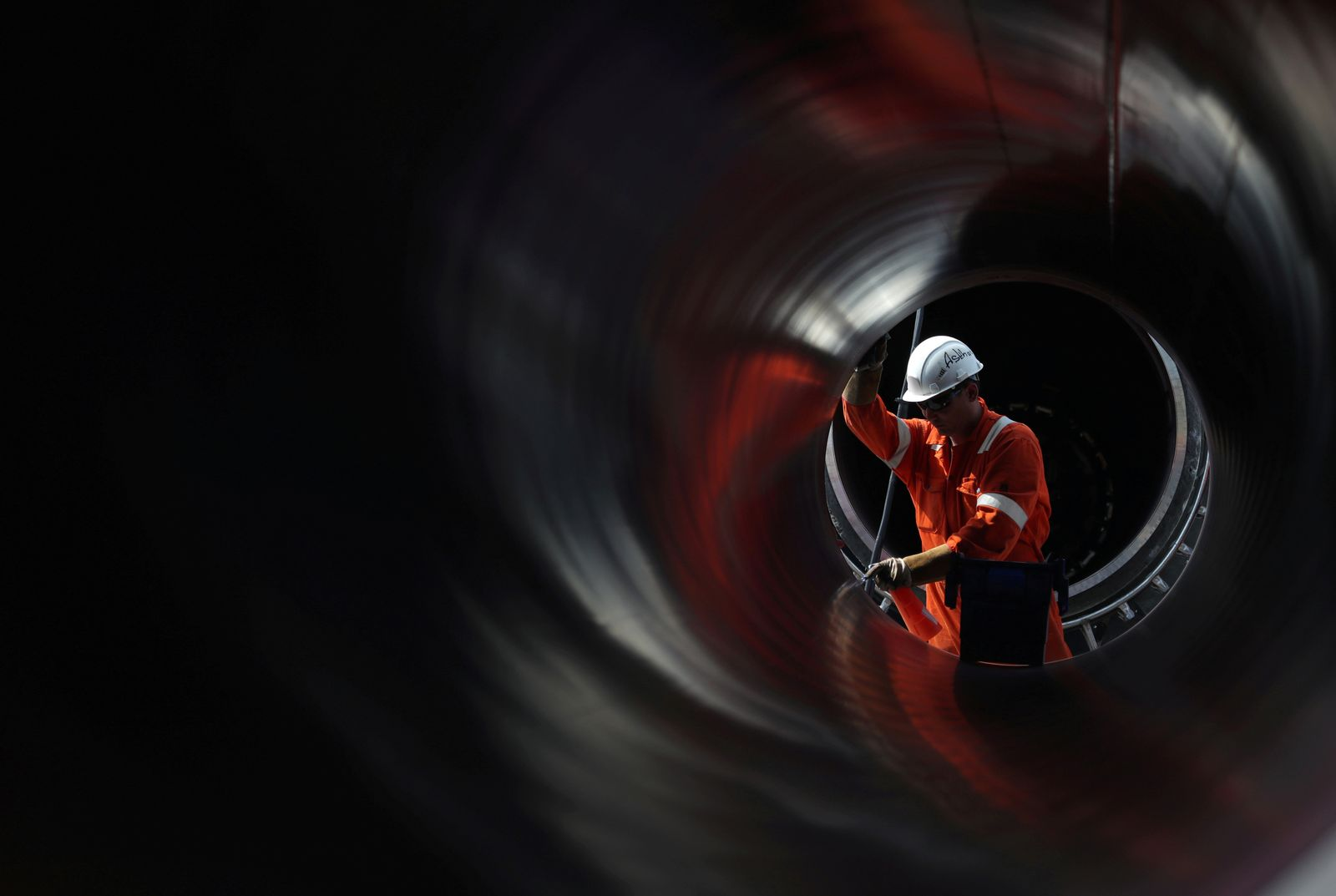FILE PHOTO: A worker is seen through a pipe at the construction site of the Nord Stream 2 gas pipeline in Russia