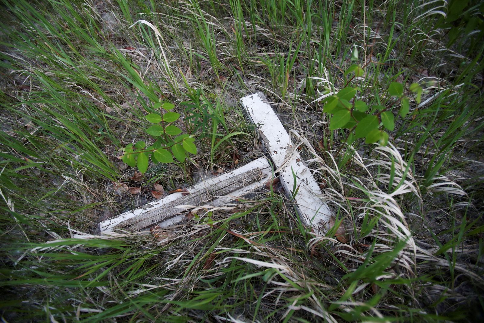 FILE PHOTO: A fallen cross at a cemetery for children who died at Brandon Indian Residential School