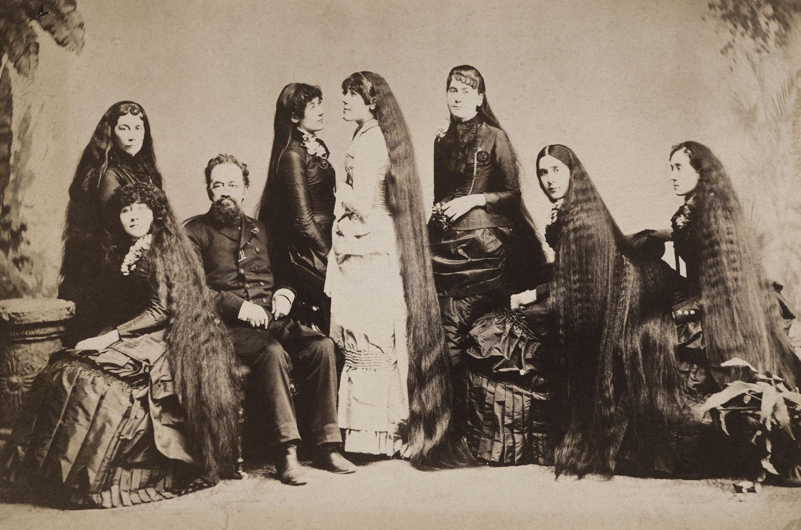 SEVEN SUTHERLAND SISTERS. The Seven Sutherland Sisters (with their father, Fletcher) of Niagara County, New York, famed for their crowning glory, the combined lengths of which was thirty-six feet, ten inches. Original cabinet photograph, c1894.