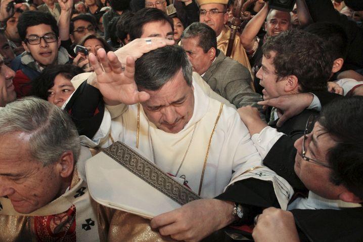Der chilenische Bischof Juan Barros umringt von Demonstranten