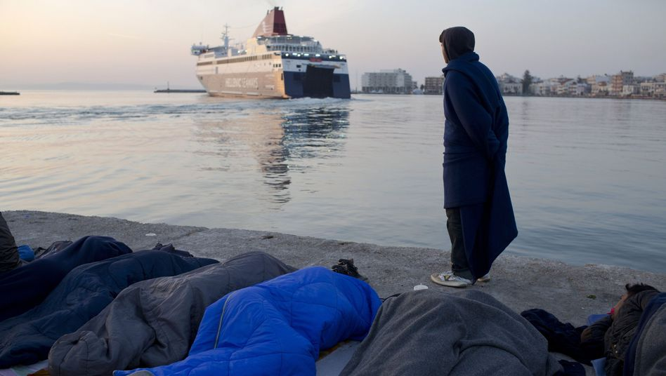 Refugees sleep on Chios as a man watches a ferry leave the Greek island. On Monday, 202 migrants from 11 countries were sent back to Turkey from the Greek islands of Lesbos and Chios.
