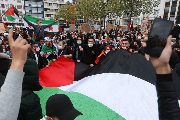 Eine palästinensische Flagge wird in Köln von mehreren Demonstranten gehalten