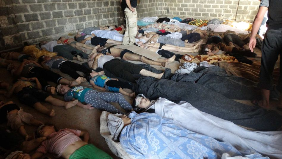 Relatives and activists inspect the bodies of people they say were killed by nerve gas in the Ghouta region, outside Damascus, on Wednesday morning.