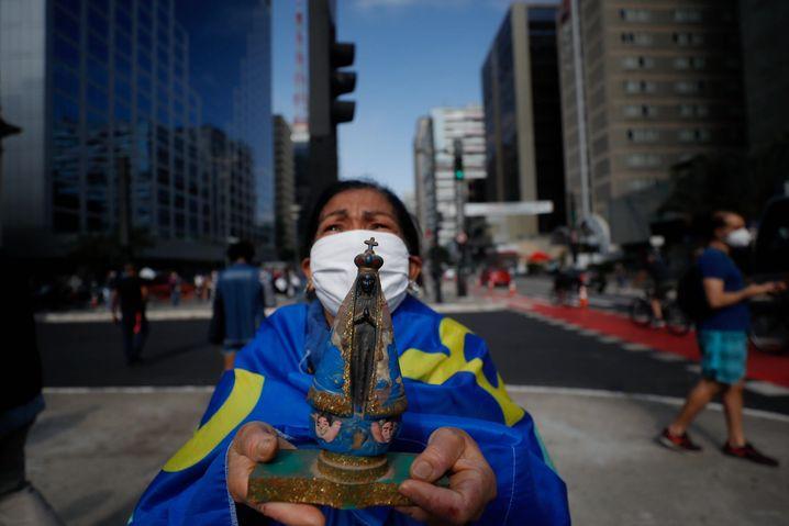 Eine Frau in São Paulo hält eine religiöse Figur in den Händen