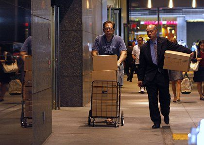 Two men walk out of the Lehman Brothers building with boxes in New York on Monday. The collapse has also threatened a major fund in Germany.