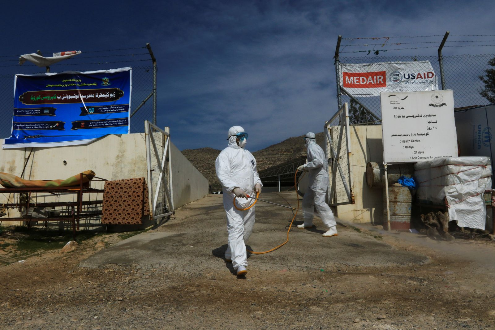 Medical staff spray disinfectant as preventive measure against the coronavirus inside the Qadia camp for Yazidi sect, on the outskirts of Dohuk province