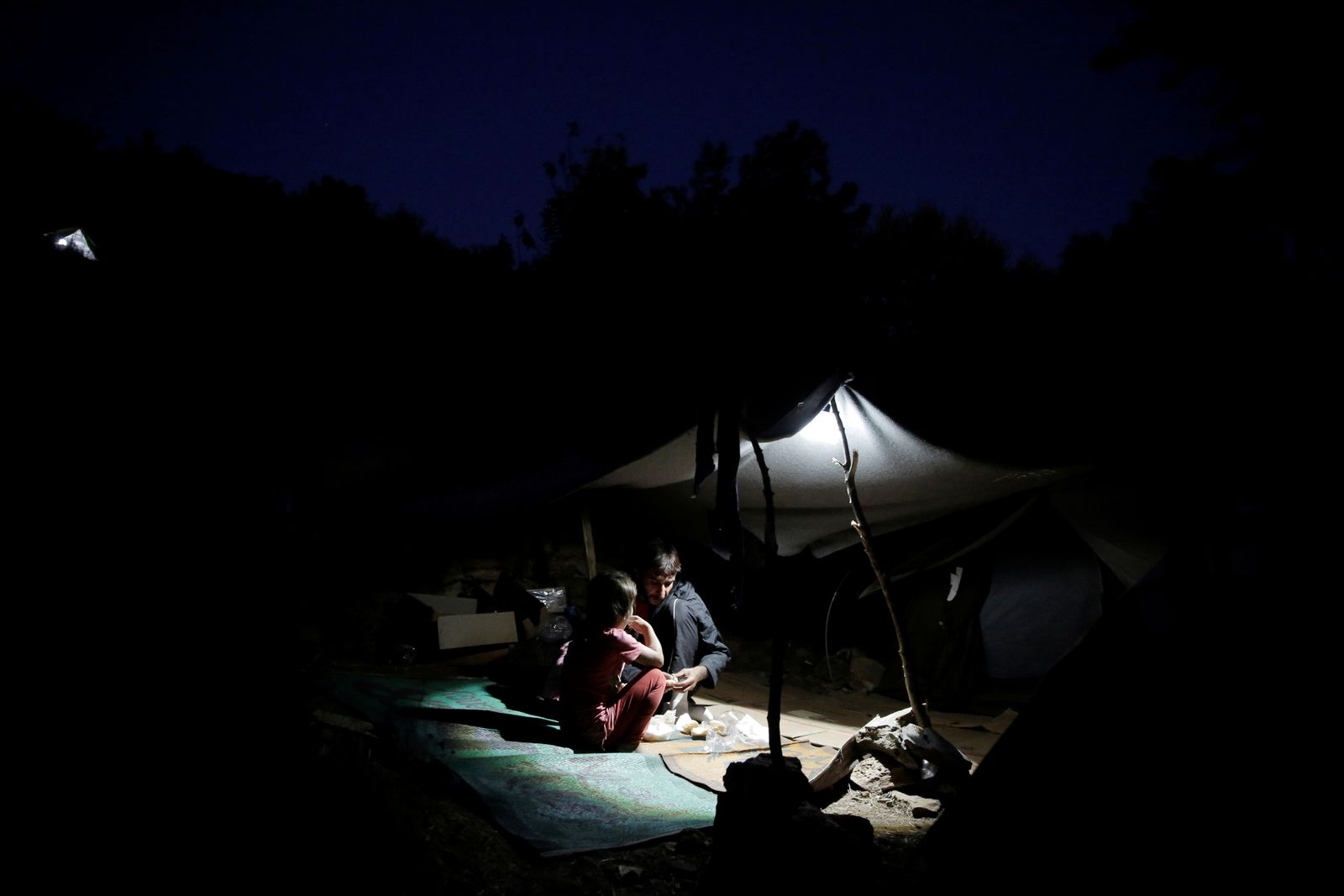 A father and his children eat under a tent at a makeshift camp on the Greek island of Samos