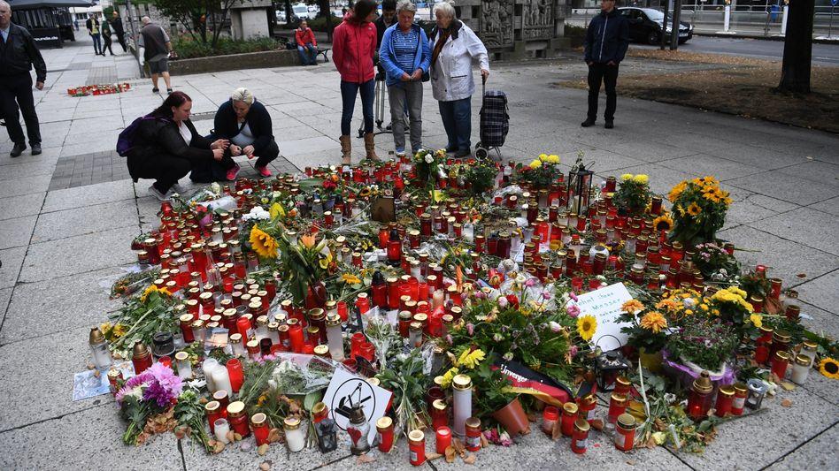 Passanten stehen am Tatort der Messerstecherei in Chemnitz