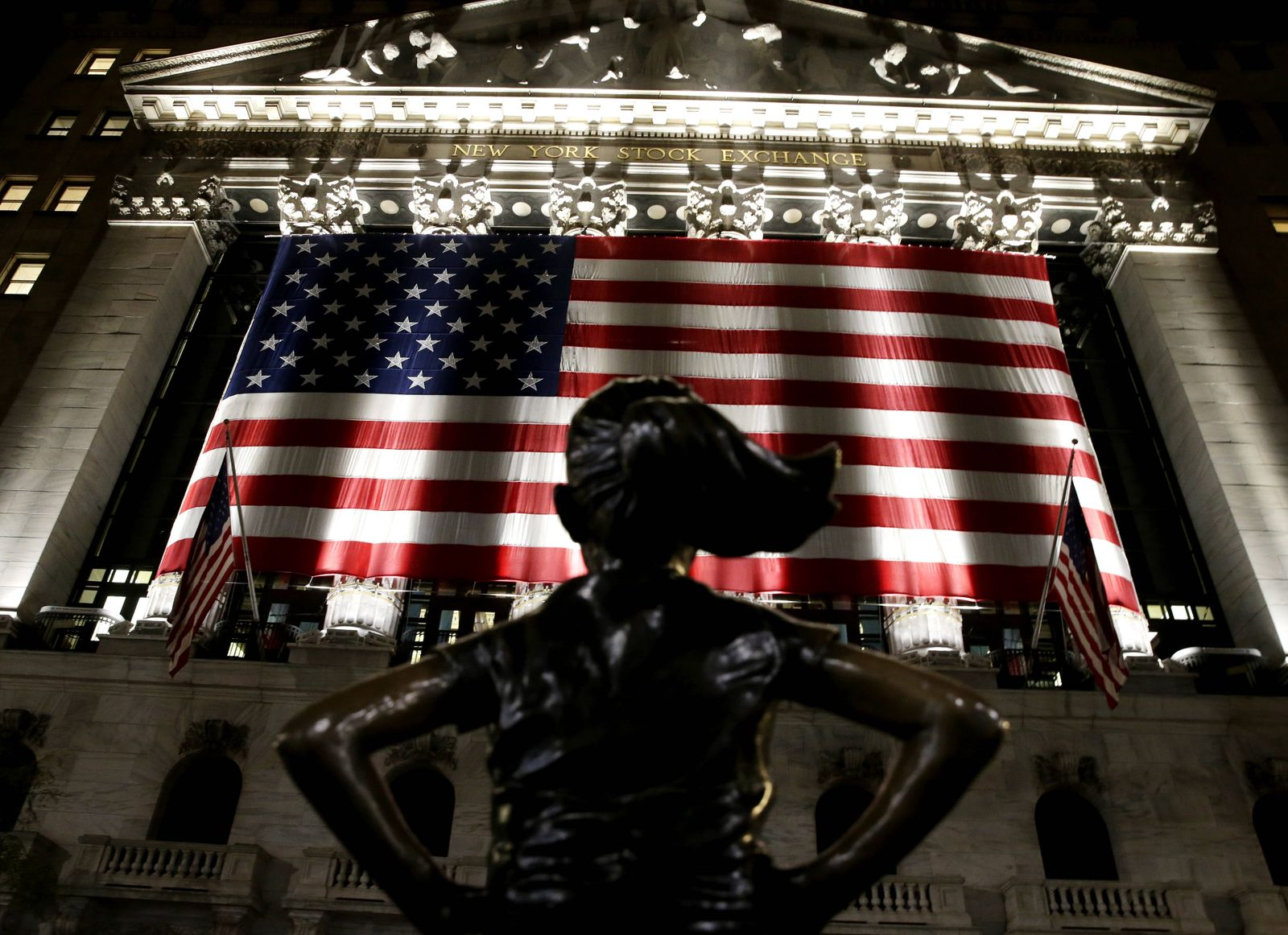The Fearless Girl Statue faces an American Flag that hangs outside at the New York Stock Exchange on Election Night on