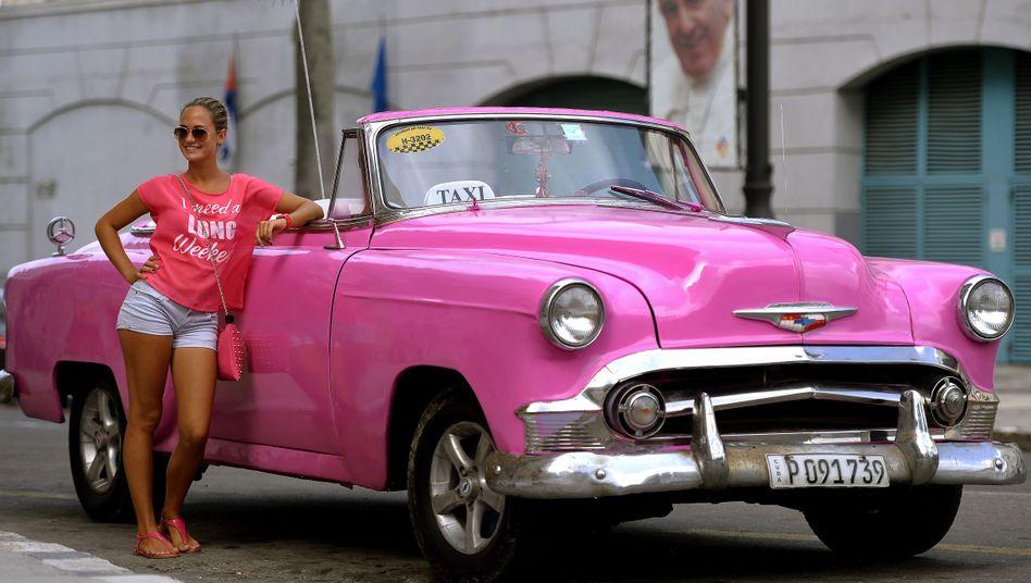 Touristin vor Taxi und Franziskus-Plakat in Havanna: Der Papst kommt