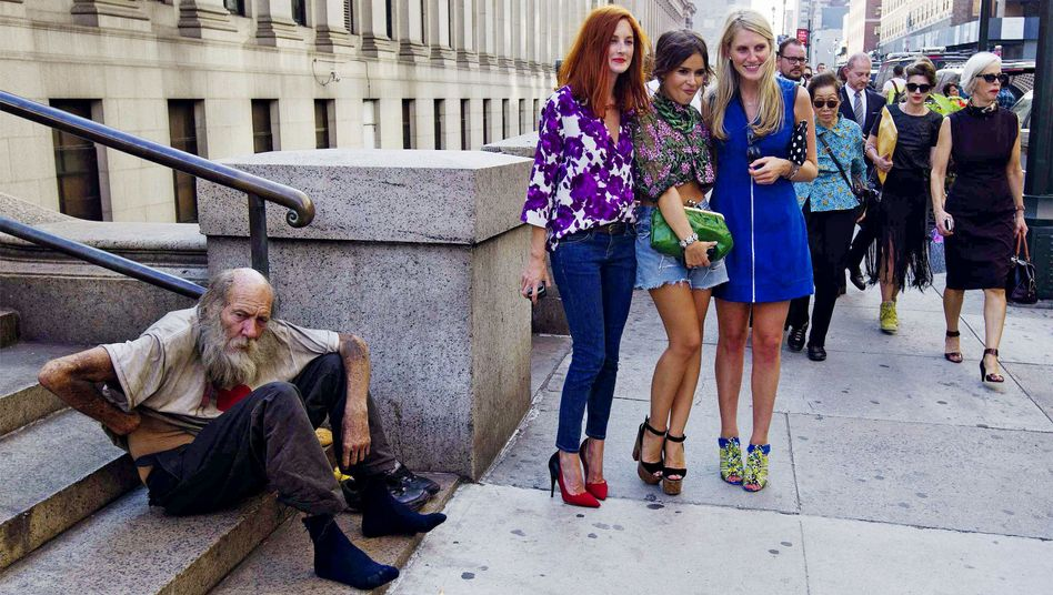 Women pose for photos near a homeless man during New York Fashion week this month.