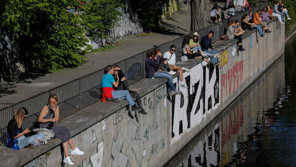 Den Sonnenschein mit Abstand genießen: Menschen sitzen am Landwehrkanal in Berlin
